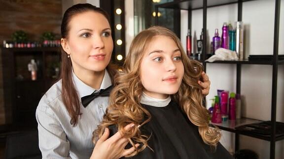 Frau mit lockigem Haar beim Friseur