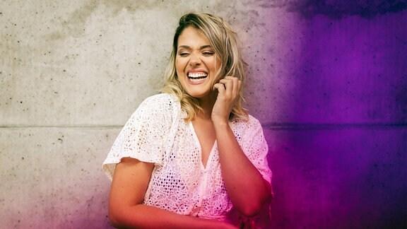 Lachende Frau steht im Freien an lilafarbener Wand.