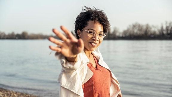 Junge Frau mit Brile an einem See