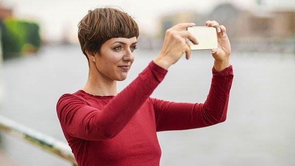 Eine Frau im roten Pullover und kurzen Haaren macht ein Selfie
