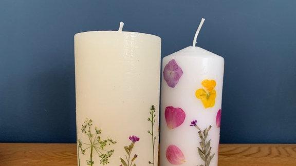 Zwei Kerzen mit Blüten gestaltet