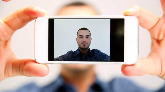 Mann hält Smartphone, das Selfie auf den Bildschirm zeigt.
