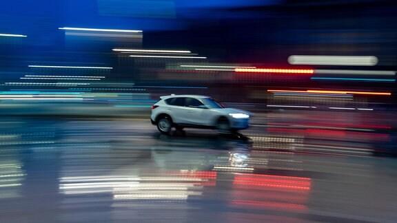 Ein Auto fährt auf regennasser Straße über den Ring in Leipzig.