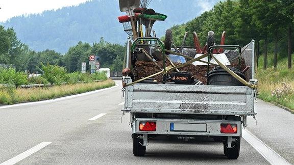 Auto mit Anhänger voll beladen mit Gartengerätschaften