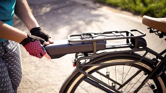Radfahrerin beim Einsetzen der Batterie an einem Elektrofahrrad