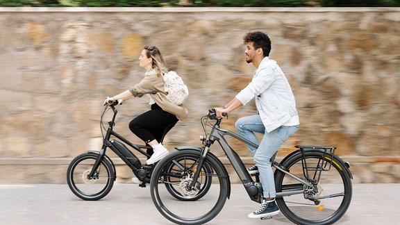 Ein Mann und eine Fraufahren auf jeweils einem Elektrofahrrad
