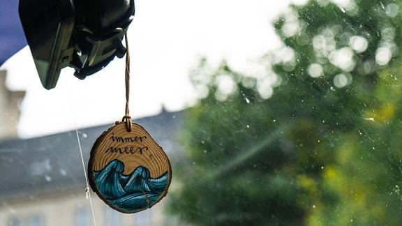 """Der Spruch """"Mehr Meer"""" auf einer Holzscheibe, die am Spiegel hängt."""