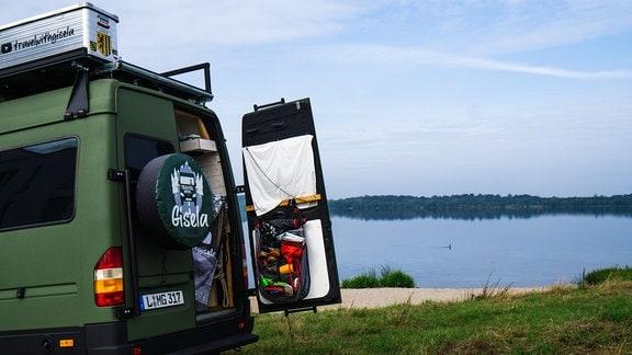 """Camper """"Gisela"""" steht mit einer offenen Hintertür am Cospudener See in Leipzig."""