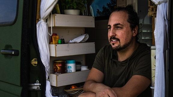 """Martin Glass lebt in seinem Camper """"Gisela"""". Auf dem Foto sitzt er in der offenen Tür des dunkelgrünen Busses und schaut in die Ferne."""