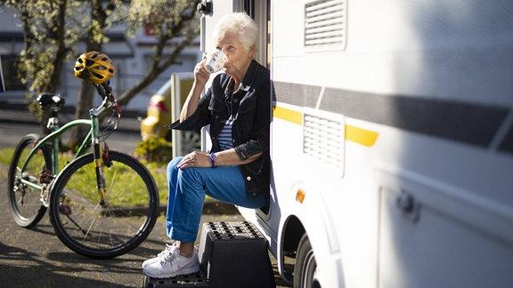 Rentnerin vor ihrem Wohnwagen