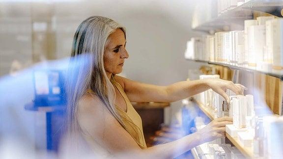 Eine Frau vor einem Kosmetikregal.