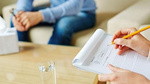 Eine Frau sitzt an einem Tisch und füllt einen Fragebogen aus.