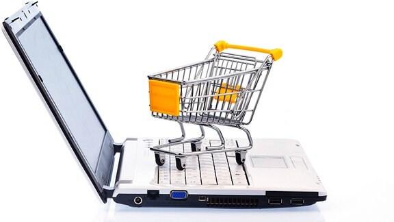 Ein kleiner Warenkorb steht auf einer Tastatur.
