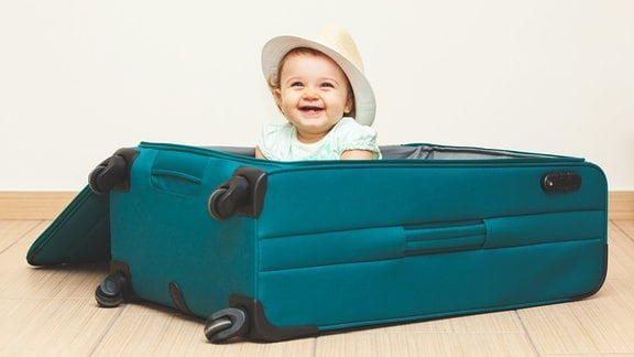 Ein Baby sitzt in einem Reisekoffer