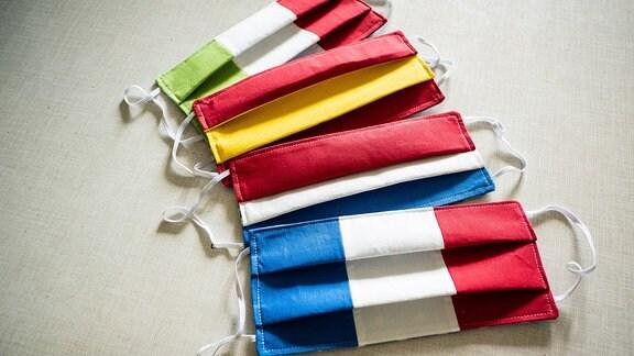 Selbstgenähte Atemschutzmasken in den Farben der Flaggen von Italien, Frankreich, Niederlande und Spanien liegen auf einem Tisch