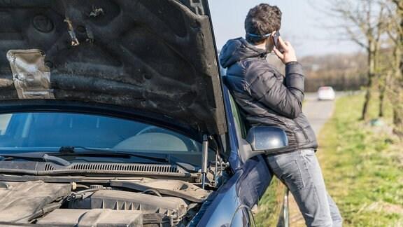 Mann telefoniert an einem Auto mit geöffneter Motorhaube lehnend.