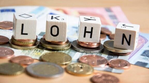 """Symbolbild von Münzen und Geldscheinen mit vier Würfeln, auf deren Vorderseiten Buchstaben stehen, die das Wort """"Lohn"""" ergeben."""