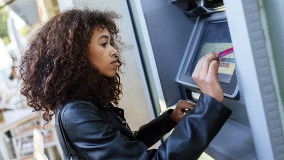Eine Frau hebt Geld am Automaten ab