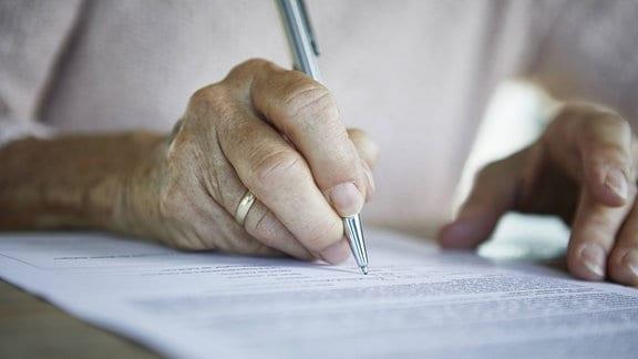 Seniorin unterzeichnet Dokument