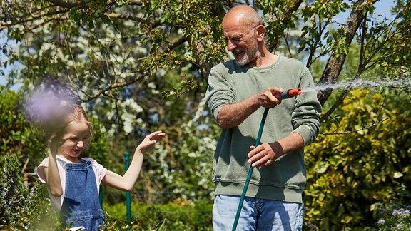 Ein Mann mit einem Gartenschlauch in einem grünen Garten