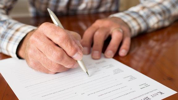 Ein Mann unterzeichnet ein Schriftstück