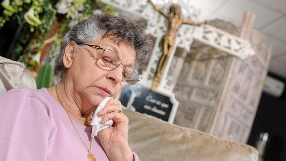 Eine ältere Dame weint und trocknet sich das Gesicht mit einem Taschentuch.