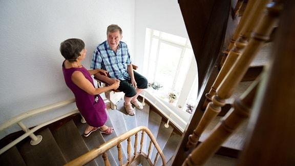 Eine Frau hält ihren an Demenz erkrankten Mann fest, während dieser einen Treppenlift benutzt.