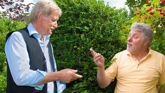 Zwei Männer vor einer Hecke