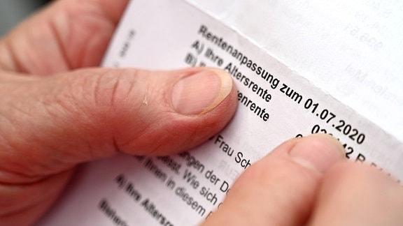 Eine Rentnerin hält ein Schreiben, das sie über die Rentenanpassung zum 1. Juli 2020 informiert