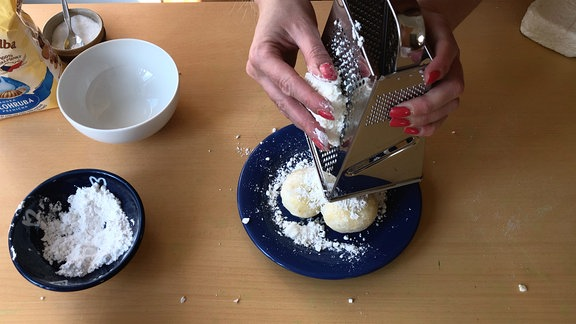 Frauenhände reiben Quark über Teller mit Knödeln