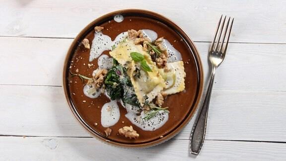 Ein ästhetisch angerichtetes Essen aus Ravioli, Spinat und Nüssen.