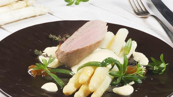 Auf einem schwarzen Teller ist ein Gericht mit Spargel angerichtet