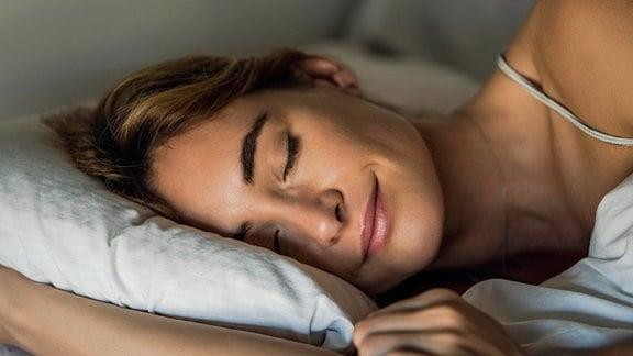 Eine junge Frau schläft im Bett