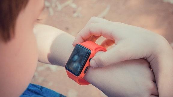 Ein Junge schaut auf seine Smartwatch.
