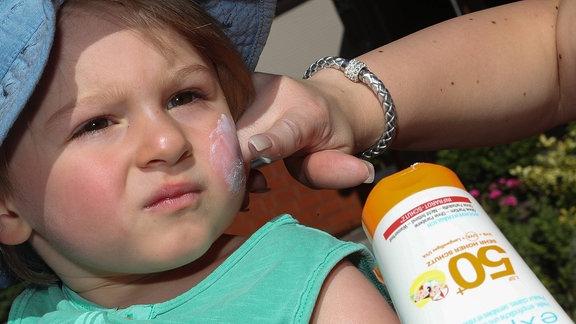Auf das Gesicht eines Kleinkinds wird Sonnencreme mit LSF 50 aufgetragen.