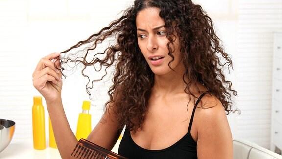 Eine junge Frau kämmt ihre lockigen Haare.