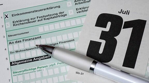 Ein Kalenderblatt vom 31. Juli liegt auf einem Steuererklärungsformular