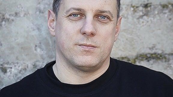 Ein Mann mit schwarzem T-Shirt und der Aufschrift 'Sächsische Tatortreinigung'.