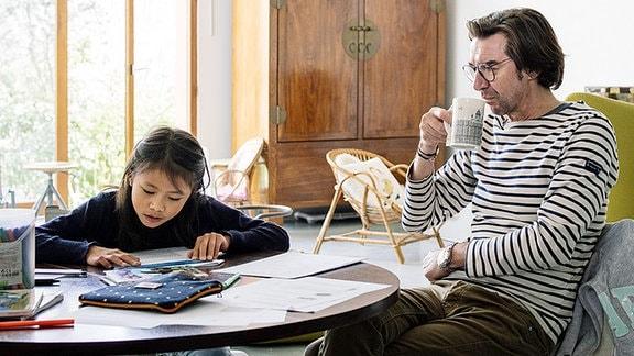 Ein Kind und ein Mann am Schreibtisch