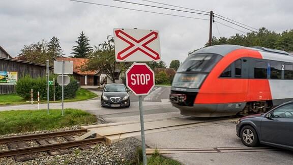 Ein Zug führt über einen unbeschrankten Bahnübergang, an dem zwei Autos warten
