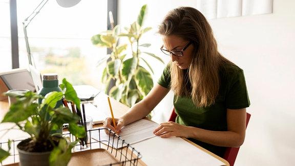 Eine Frau arbeitet an einem Schreibtisch, umgeben von Zimmerpflanzen
