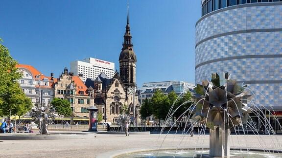 """Richard-Wagner-Platz mit Pusteblumen-Brunnen und der """"Blechbüchse"""", dahinter die Evangelisch-Reformierte Kirche am Tröndlinring"""