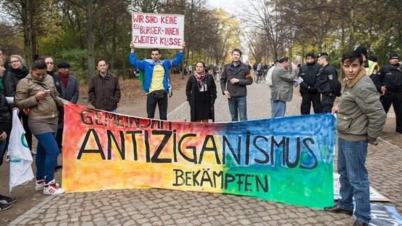 """Demonstranten halten ein Plakat, auf dem steht: Gemeinsam Antiziganismus bekämpfen"""""""