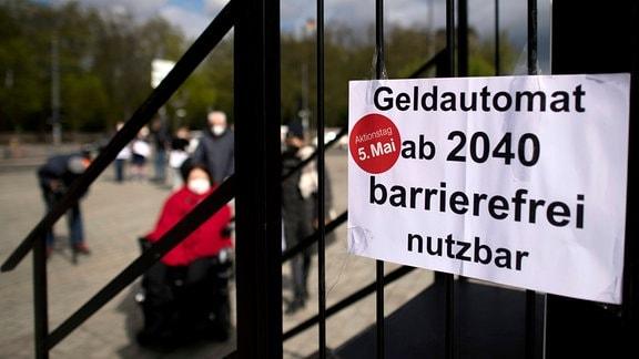 Demonstranten vor ironischem Schild 'Geldautomat ab 2040 barrierefrei nutzbar'