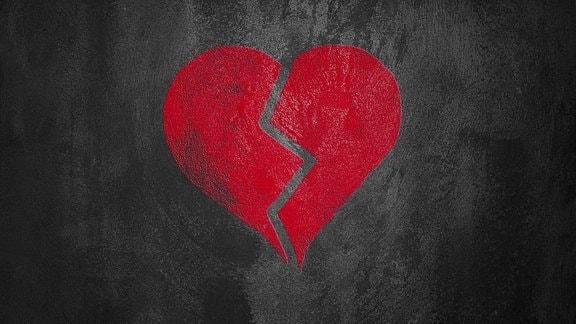 Ein rotes, zebrochenes Herz auf schwarzem Hintergrund.