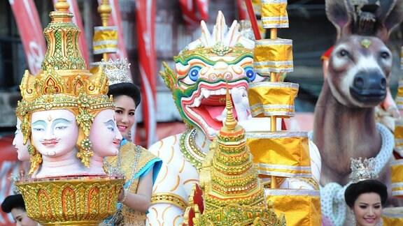 Eine Frau schaut lächelnd hinter einer Buddhastatue hervor