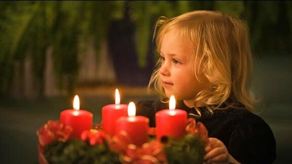 Ein blondes Mädchen neben einem Adventskranz, auf dem vier Kerzen brennen