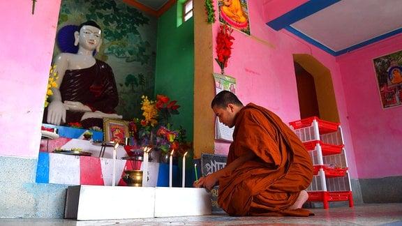 Ein Mönch zündet vor einer Buddha-Statue Kerzen an