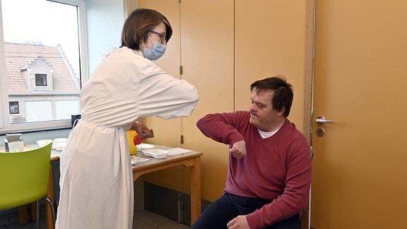 Ärztin begrüß einen Menschen vor Beginn der Impfung.