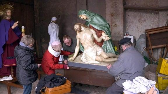 Menschen hantieren an einer Holzfigur
